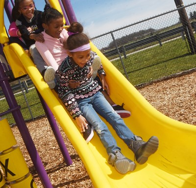 From top, CES first-graders Daya Griffin, Priyanka Flores and Zaylin Johnson slide together on the playground.