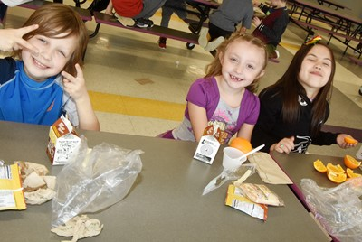 From left, CES first-graders Dehren Rinesmith, Zaylee Shietze and Rinoa Ramsey enjoy lunch together.
