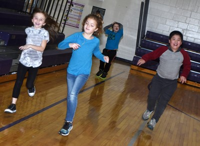From left, CES second-grader Tabitha Leggett, Mae Miller and William Li run together in their PE class.