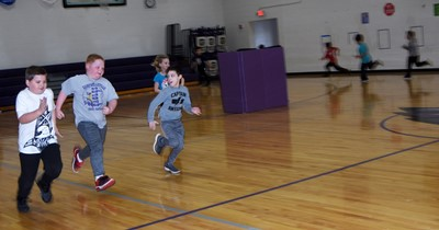 CES second-graders Honor Ramsey, at left, and Konnar Hicks run with their classmates in PE class.