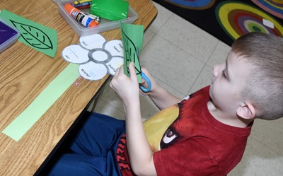 CES kindergartener Kaiden Miller cuts out his leaves.