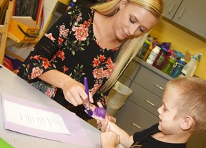 CES preschool assistant Tesa Novak helps Joseph Welch paint his hand as he makes his card.
