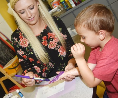CES preschool assistant Tesa Novak helps Carter Murray paint his hand as he makes his card.