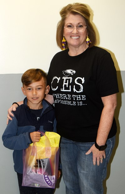 CES Guidance Counselor Donna White presents second-grader Phoenix Lawler a prize for tying a friend's shoes on Random Acts of Kindness Day.