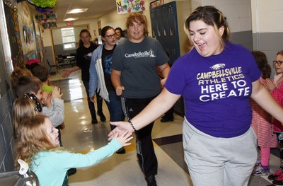 CHS senior Brandy Miller high-fives CES students as she participates in the Eagle Walk.