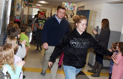 CHS senior Conner Riley, at left, and Campbellsville Middle School eighth-grader Layla Steen high-five CES students as they participate in an Eagle Walk.