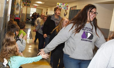 Campbellsville Middle School eighth-grader Allison Sumners high-fives CES students as she participates in an Eagle Walk.