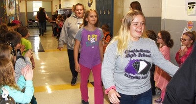 CHS junior Riley Rainwater high-fives CES students as she and her fellow band members participate in an Eagle Walk.