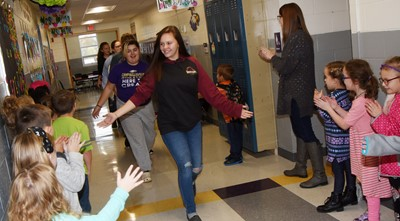 CHS junior Mystique Jones high-fives CES students as she and her fellow band members participate in an Eagle Walk.