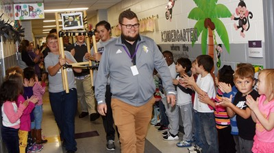 CHS marching band director Cameron Johnson leads his band members down the CES hallways in an Eagle Walk.