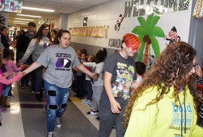 From left, CHS freshman Kadence Houk, Campbellsville Middle School eighth-grader K.J. Forbis and iEagle seventh-grader Ivy Lawler walk down the CES hallways in an Eagle Walk.