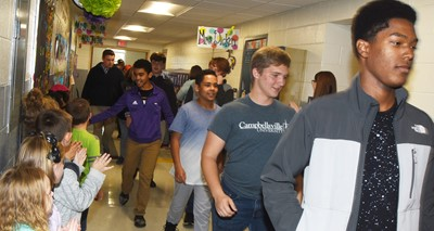 From left, Campbellsville Middle School seventh-grader Gabriel Noyola, eighth-grader Diego Noyola, CHS senior Tristin Lopez and junior Zaquan Cowan participate in an Eagle Walk down the CES hallways.