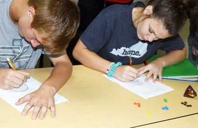 CHS freshmen Andrew Butler, at left, and Tatum Bridgewater graph their data to show the color of their m&m candies.