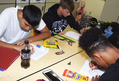 From left, CHS freshman Mark Contreras and juniors Blase Wheatley and Reggie Thomas graph their data to show the color of their m&m candies.