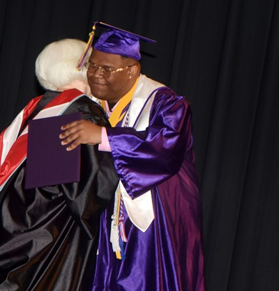 Campbellsville Board of Education Chair Pat Hall hugs Jeremiah Jackson.