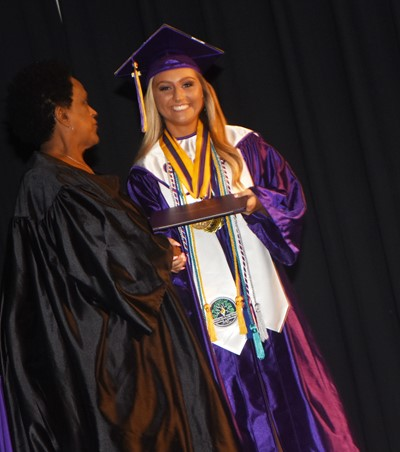 Campbellsville Board of Education member Barkley Taylor gives Reagan Knight her diploma.