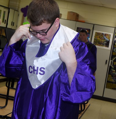 CHS senior John Netherland fixes his gown as he prepares to graduate.