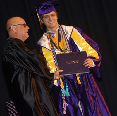 Campbellsville Board of Education member Mitch Overstreet gives Myles Murrell his diploma.