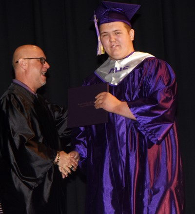 Campbellsville Board of Education member Mitch Overstreet gives Jorden Perkins his diploma.
