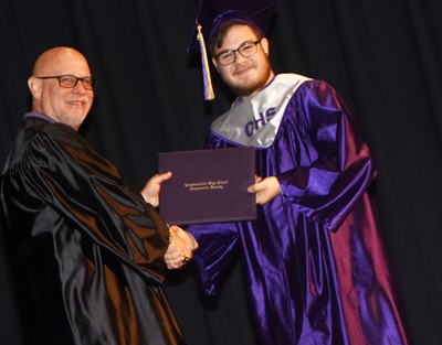 Campbellsville Board of Education member Mitch Overstreet gives Kyler Rakes his diploma.