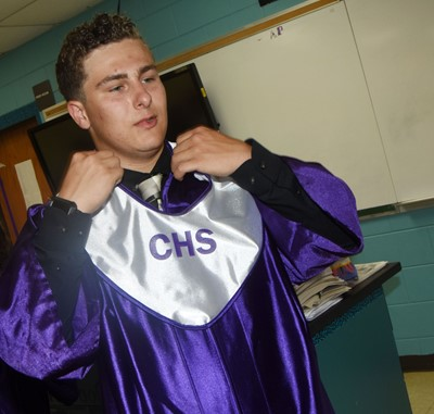 CHS senior Brody Weeks fixes his gown as he prepares to graduate.