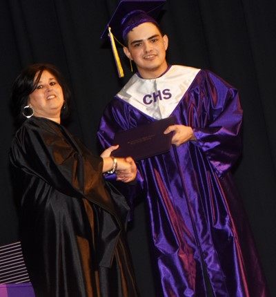 Campbellsville Board of Education Vice Chair Suzanne Wilson gives Seth Tindal his diploma.