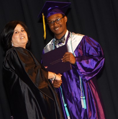 Campbellsville Board of Education Vice Chair Suzanne Wilson gives Daesean Van Cleave his diploma.