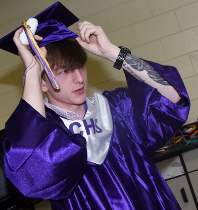 CHS senior Merick Turner fixes his cap as he prepares to graduate.