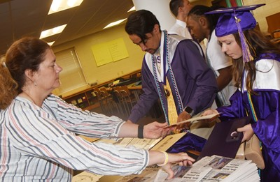 CHS teacher Tammy Wilson hands out diplomas to Glenn Lamer, at left, and Christa Riggs.