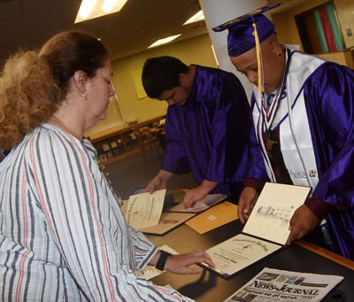 CHS teacher Tammy Wilson hands out diplomas to senior Nick Cowan, at left, and Dee Simpson.
