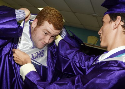 CHS senior Spencer Swafford fixes his gown, with help from classmate Evan McAninch.