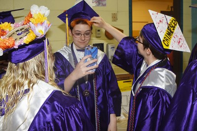 From left, CHS seniors Jessie Bennett, Chloe Decker and Christina Phipps prepare for their graduation ceremony.