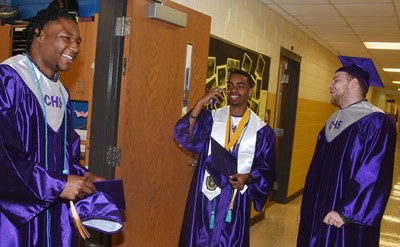 From left, CHS seniors Taj Sanders, Davon Cecil and Dakota Reardon share a laugh before their graduation ceremony.