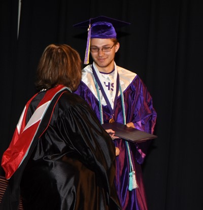 Campbellsville Board of Education member Angie Johnson gives Keidlan Boils his diploma.