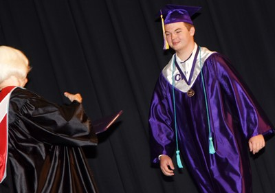 Campbellsville Board of Education Chair Pat Hall gives Josh Dooley his diploma.