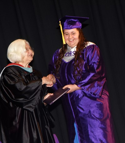 Campbellsville Board of Education Chair Pat Hall gives Amanda Dotson her diploma.