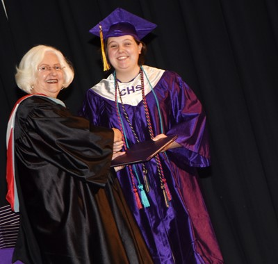 Campbellsville Board of Education Chair Pat Hall gives Ruby Hatfield her diploma.