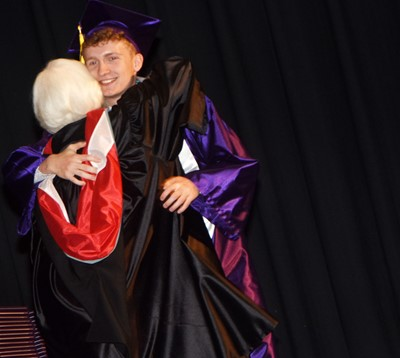 Campbellsville Board of Education Chair Pat Hall hugs Jackson Hinton.