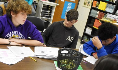 From left, CHS freshman Weston Mattingly and sophomores Cohen Moon and Adrien Smith discuss the poem Half-Hanged Mary with their classmates.