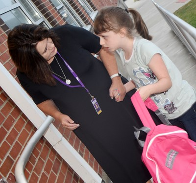 CES teacher Denise Spencer greets second-grader Kaylee Franklin.