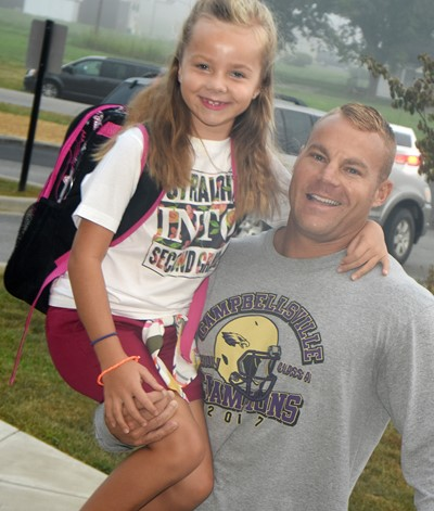 Robbie Gribbins carries his daughter, Trinidy, as she begins her first day of second grade.