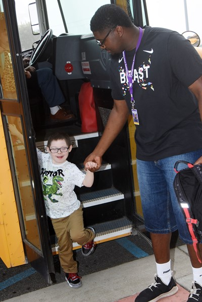 CES instructional assistant Allen Costley helps third-grader Nicholas Brunner off the bus as he arrives at school.