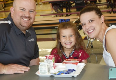 CES kindergartener Olivia Pavy enjoys breakfast with her parents, E.J. and Anna Marie.