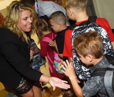 CES Principal Elisha Rhodes high-fives her students as they start their day.