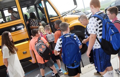 CES art teacher Adrienne Hash helps iEagle students board the bus for the first day of class.