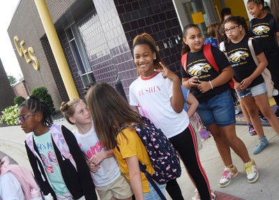 iEagle student Aliy Dunn, a fourth-grader, is all smiles as she and her classmates board the bus for the first day.