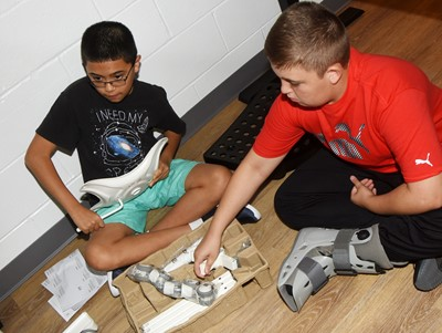 iEagle students Jacob DeBrot, at left, and Skylar Wilhoite, seventh-graders, work together to put a chair together.
