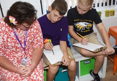 iEagle teacher Tracey Rinehart talks with fifth-graders Aidan Wilson, center, and Joseph Greer as they do a word search to learn their classmates' names.
