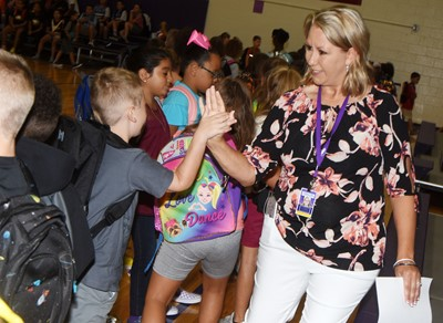 CES teacher Amanda Greer greets her second-grade students as they walk to their classroom to begin the first day of school.