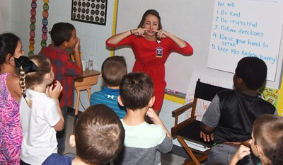 CES second-grade teacher Emily Andrew sings and dances with her students.